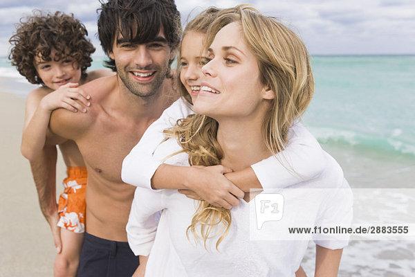 Ein Paar  das seine Kinder am Strand huckepack fährt.