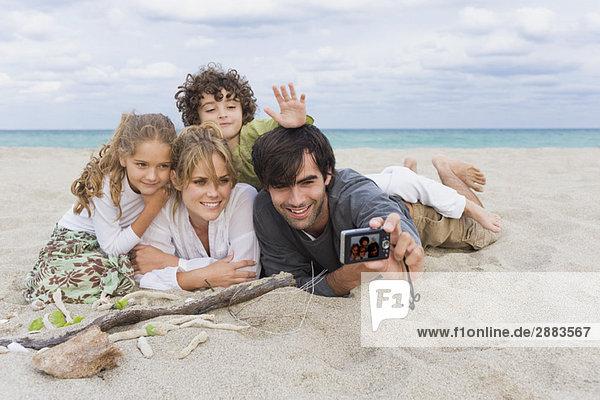 Ein Mann fotografiert seine Familie mit einer Digitalkamera am Strand.