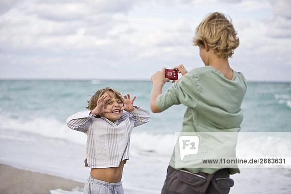 Junge fotografiert seinen Bruder mit einer Digitalkamera