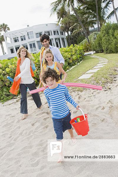 Familienwanderung am Strand mit einem Touristenort im Hintergrund