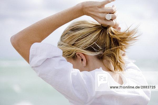 Frau setzt Haare in Pferdeschwanz
