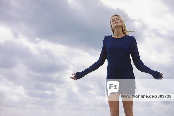 Frau stehend mit ausgestrecktem Arm