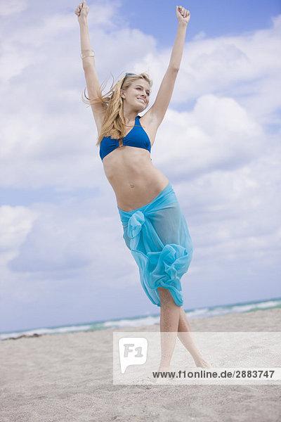 Frau steht mit erhobenen Armen am Strand.