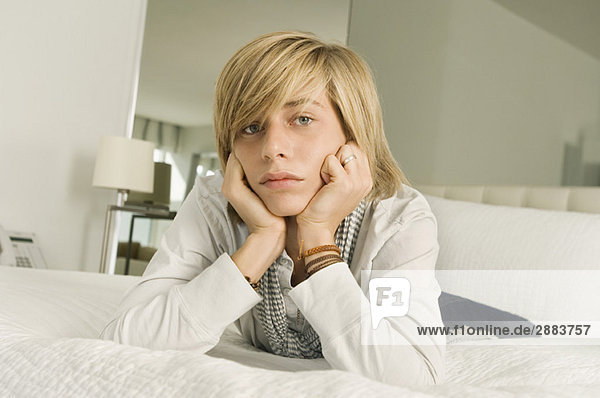 Teenage boy lying on the bed and looking serious
