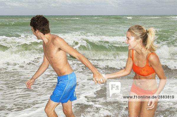 Paar hält sich an den Händen und geht am Strand spazieren.