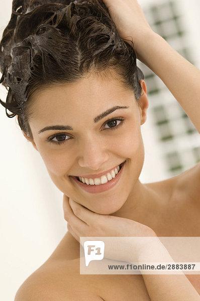 Porträt einer Frau beim Haarewaschen