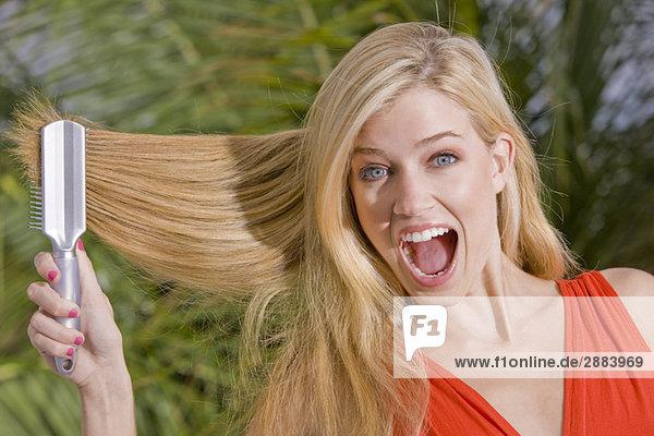 Frau bürstet sich die Haare und schreit.