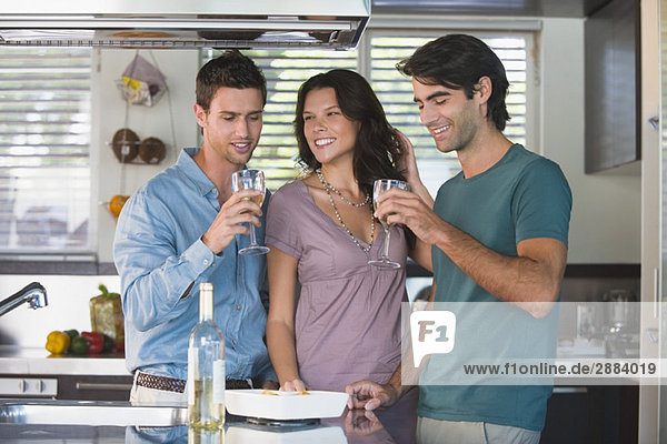 Drei Freunde trinken Wein in der Küche
