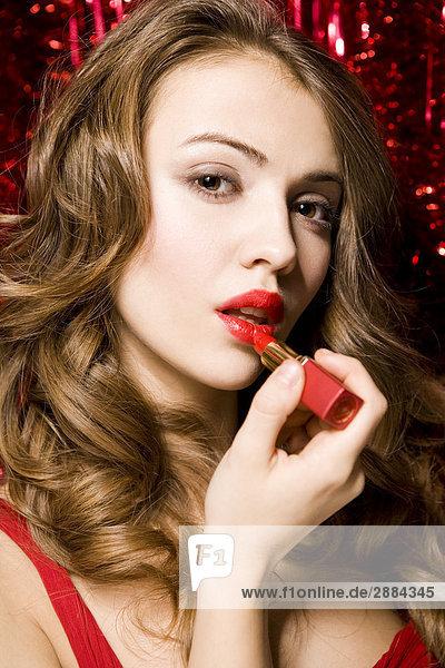 Frau trägt roten Lippenstift auf