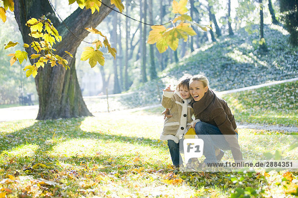 mother and daughter throwing leaves in park