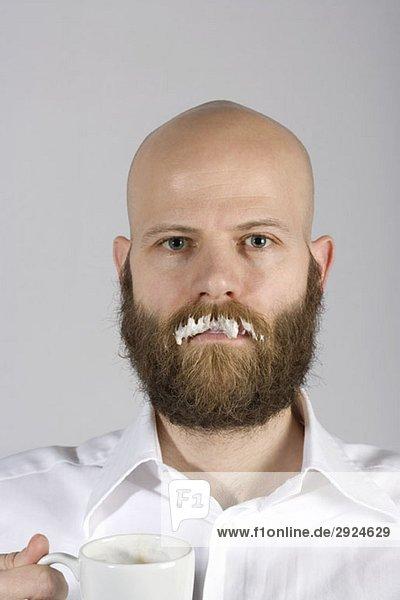 Ein Mann mit einem Milchbart auf seinem echten Schnurrbart.
