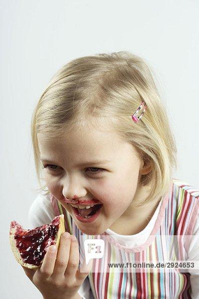 Ein junges Mädchen kichert beim Essen von Brot und Marmelade.
