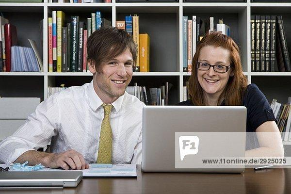 Ein Geschäftsmann und eine Geschäftsfrau  die mit einem Laptop arbeiten.