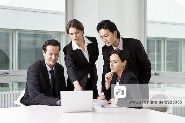 Vier Geschäftsleute in einer Besprechung mit einem Laptop