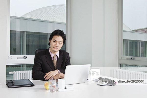 Porträt eines Geschäftsmannes  der an seinem Schreibtisch sitzt