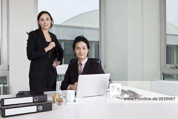 Ein Geschäftsmann und eine Geschäftsfrau  die auf einen Laptop schauen.