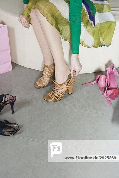 Eine junge Frau probiert in einem Laden Schuhe an.