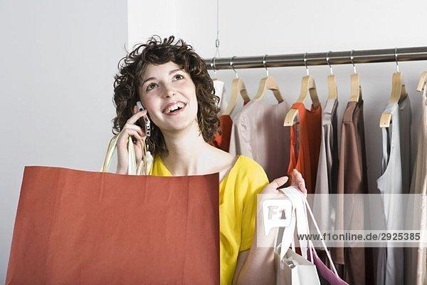 Eine junge Frau  die ihr Handy in einem Bekleidungsgeschäft benutzt.