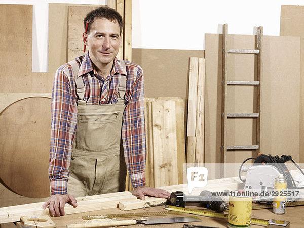 Porträt eines in einer Holzwerkstatt stehenden Mannes