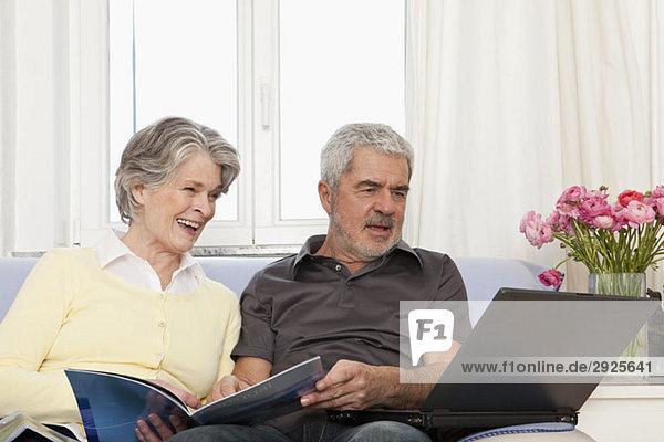 Eine ältere Frau und ein älterer Mann  die einen Laptop benutzen.