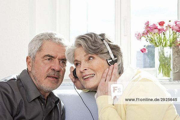Eine ältere Frau  die ihre Kopfhörer teilt  damit ein älterer Mann zuhören kann.