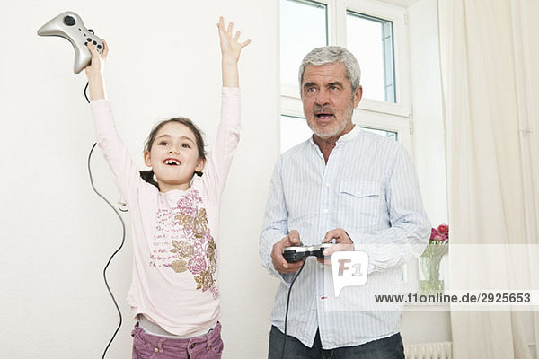 Ein Großvater und seine Enkelin spielen ein Videospiel.