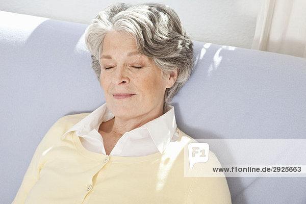 Eine ältere Frau  die auf einer Couch schläft.