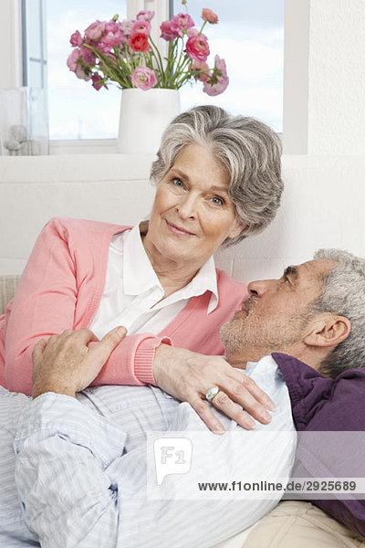 Ein älterer Mann und eine ältere Frau liegen zusammen auf einer Couch.