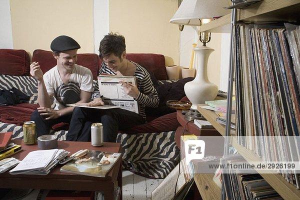 Zwei junge Männer  die sich auf einem Sofa Rekorde ansehen.