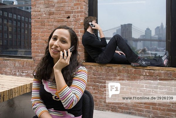 Two people talking on mobile phones in a modern apartment