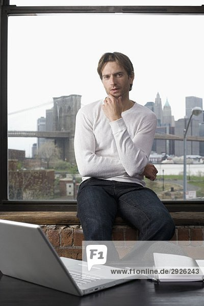 Man sitting on a window sill with laptop and diary