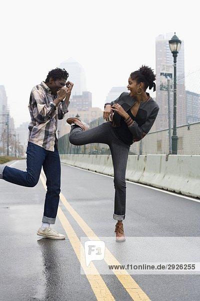 Ein Mann und eine Frau  die auf einer Straße stehen und kämpfen.