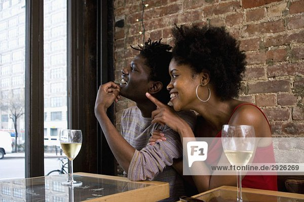 Ein junges Paar sitzt in einem Restaurant mit Gläsern Weißwein.