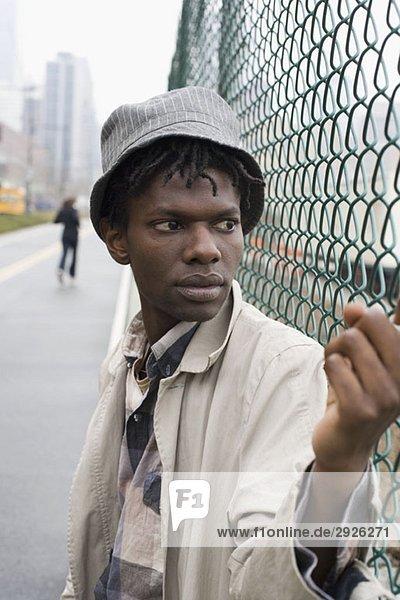 Ein junger Mann  der sich an einen Zaun lehnt.