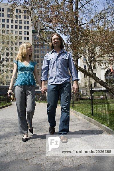 Ein junges Paar  das durch einen Stadtpark geht und Händchen hält  Central Park  New York City
