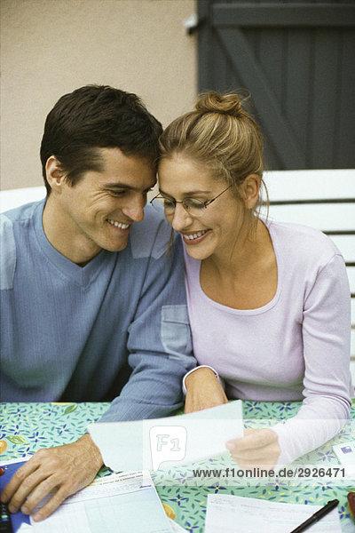Paar sitzt am Tisch  diskutiert über Finanzen  beide lächelnd