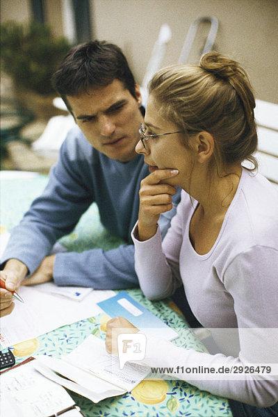 Ein Paar sitzt am Tisch und bespricht Rechnungen.