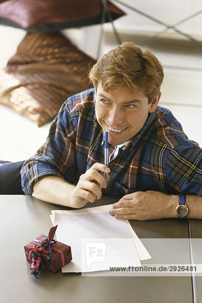 Man sitting at table writing letter  gift nearby