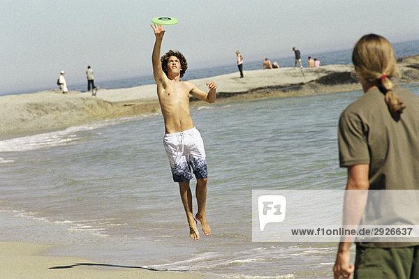 Zwei Freunde am Strand werfen Frisbee  einer springt zum Fangen.
