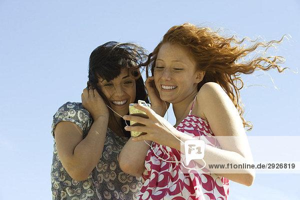 Zwei junge Frauen im Freien  die zusammen einen MP3-Player hören.
