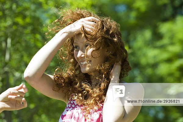 Junge Frau mit roten Haaren an windigen Tagen im Freien