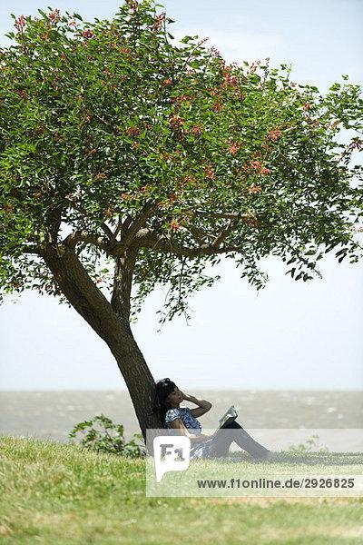 Junge Frau sitzt unter Baum  liest Buch