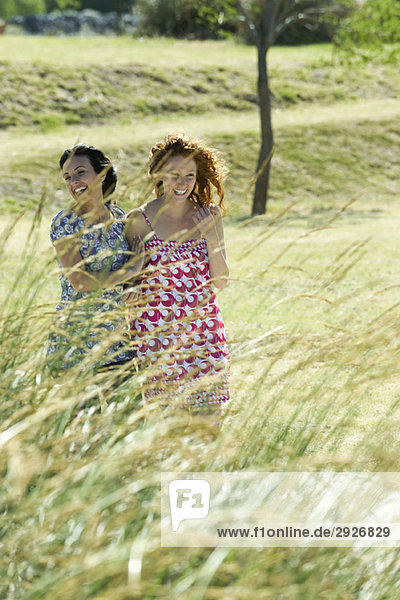 Two young women laughing together outdoors  tall grass in foreground