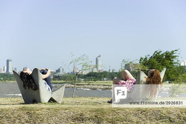 Zwei junge Frauen entspannen sich in Stühlen  Teich und Stadtsilhouette im Hintergrund