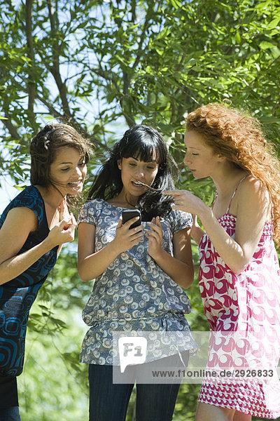 Drei junge Frauen  die im Freien stehen und auf das Smartphone schauen.