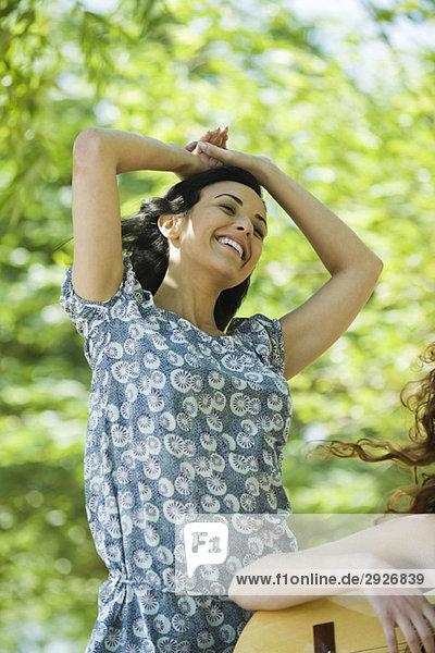 Junge Frau steht draußen mit Händen auf dem Kopf  lächelnd  Freundin spielt Gitarre in der Nähe