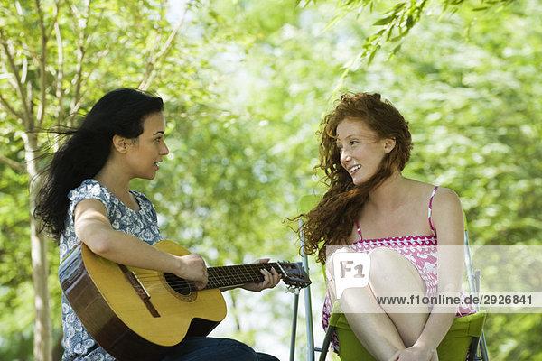Zwei junge Frauen sitzen im Freien  eine spielt Akustikgitarre.