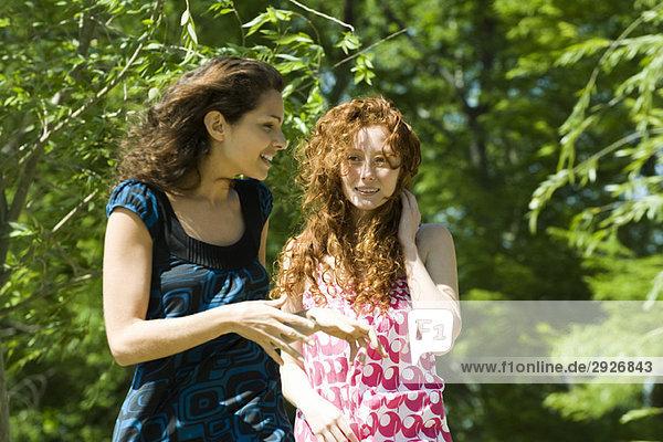 Zwei junge Frauen  die im Freien spazieren gehen und sich unterhalten.