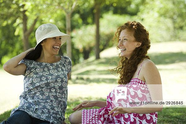 Zwei junge Frauen plaudern im Freien  beide lächelnd.