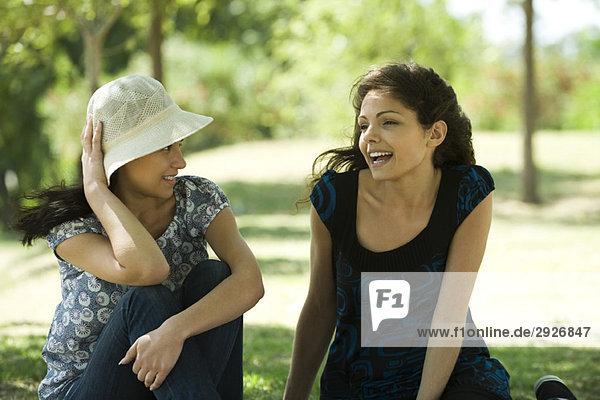 Zwei junge Frauen reden im Freien  eine hält einen Sonnenhut auf dem Kopf.